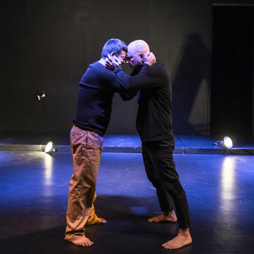 Two actors closely face each other, closely holding one another by their necks during the performance