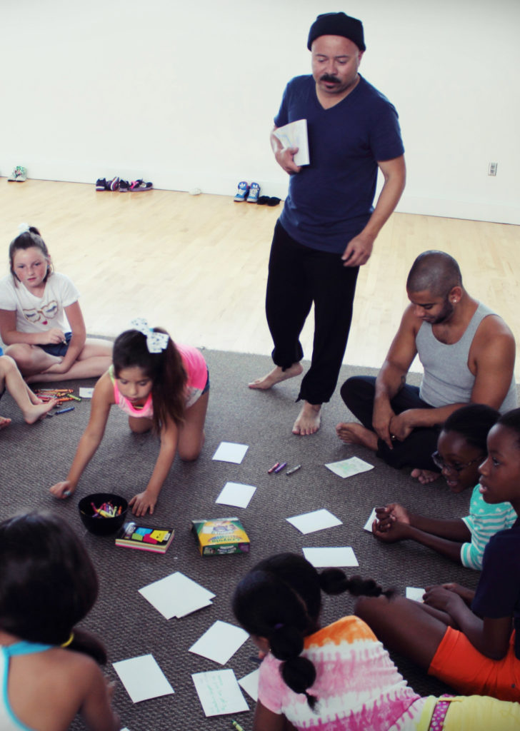 A group of kids play and interact with educators during the workshop.
