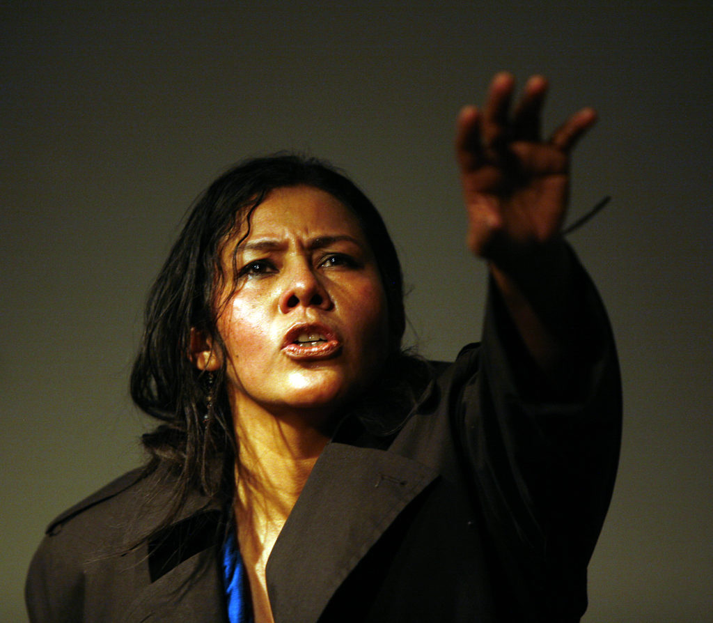 Actress looks ahead reaching out during the performance